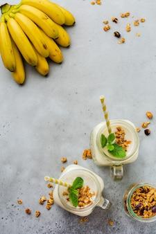 Smoothie à la banane avec granola, fruits secs et menthe sur une surface de béton gris