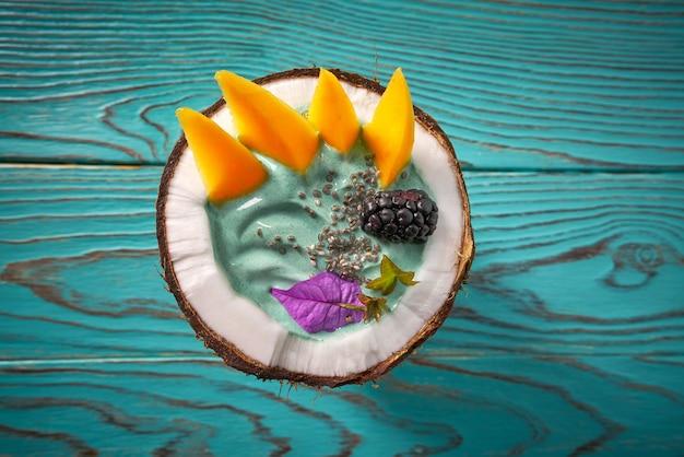 Smoothie bol à la spiruline à la mangue, noix de coco et mûres