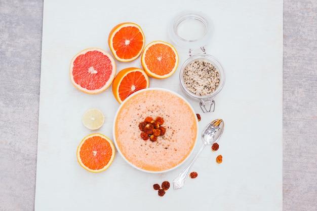 Smoothie bol avec des tranches ou d'orange, citron vert ou de pamplemousse, graines de chanvre, une cuillère.