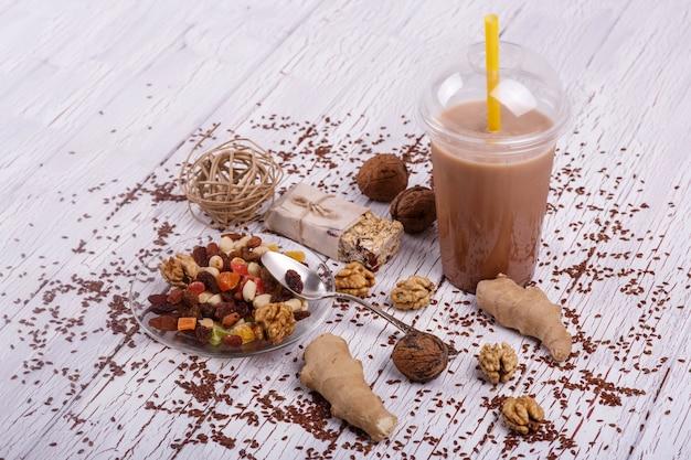 Un smoothie brun sain avec du noyer et des fruits confits repose sur la table