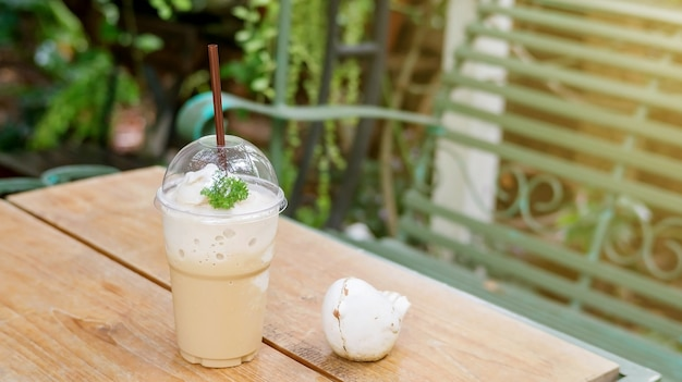 Smoothie café sur une table en bois et fond de la plante.