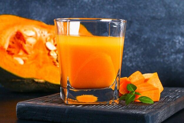 Smoothie citrouille jus de citrouille sur une table sombre. boissons d'automne.