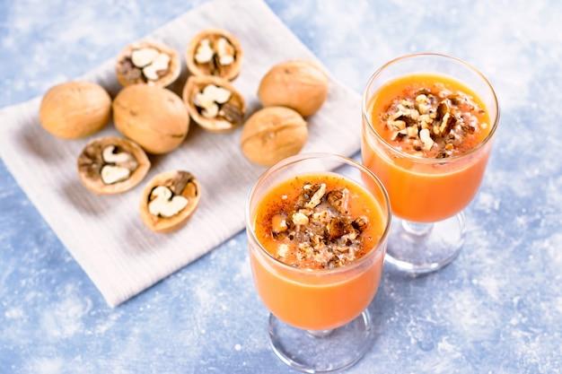Smoothie citrouille sain aux noix et cannelle dans des verres sur fond rustique