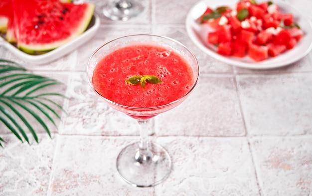 Smoothie cocktail d'été rafraîchissant à la pastèque avec des tranches et des morceaux de pastèque en arrière-plan