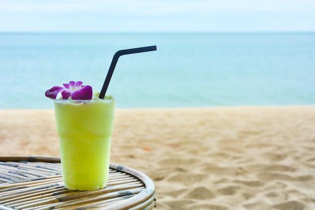 Smoothie de couleur verte avec orchidée pourpre sur la table en bois avec le beau fond de mer