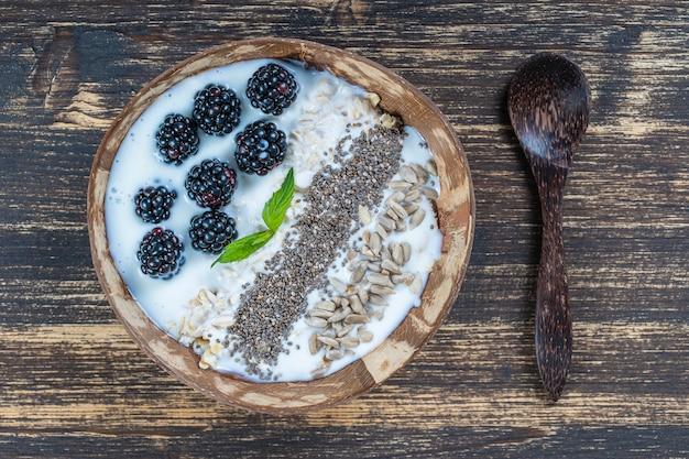 Smoothie dans un bol de noix de coco avec mûres, flocons d'avoine, graines de tournesol et graines de chia pour le petit-déjeuner, gros plan. le concept d'une alimentation saine, superaliments. vue de dessus