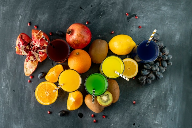 Smoothie frais froid pressé à partir de différents fruits exotiques tropiques tels que raisins, citron orange, kiwi et grenats