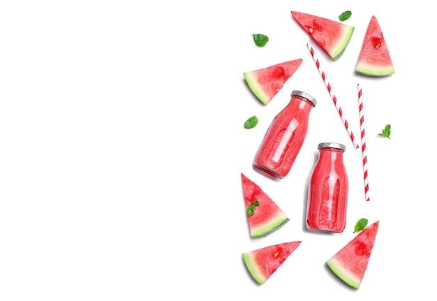 Smoothie frais et savoureux à la pastèque dans des bouteilles en verre isolées sur fond blanc. vue de dessus. espace de copie.
