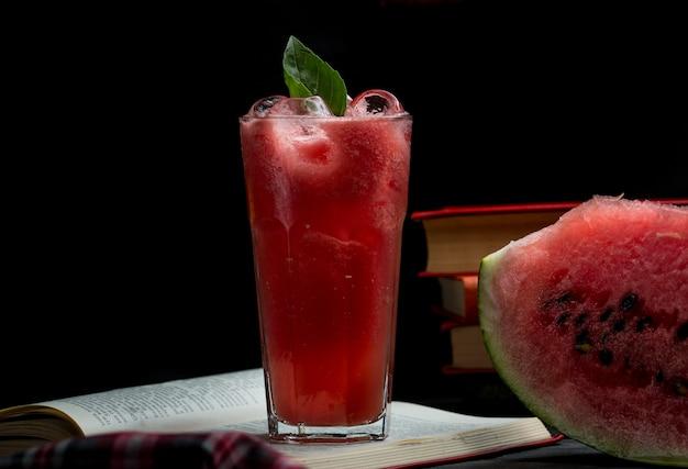 Smoothie glacé de melon d'eau avec des feuilles de menthe et une tranche de melon d'eau