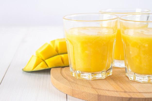 Smoothie jaune de mangue, banane et orange sur une table en bois blanche.