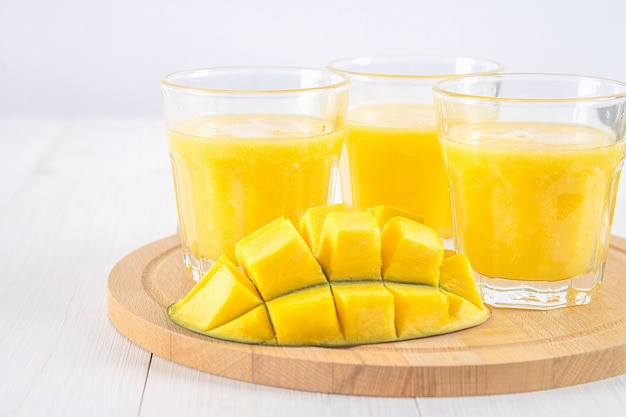 Smoothie jaune de mangue, banane et orange sur une table en bois blanche.