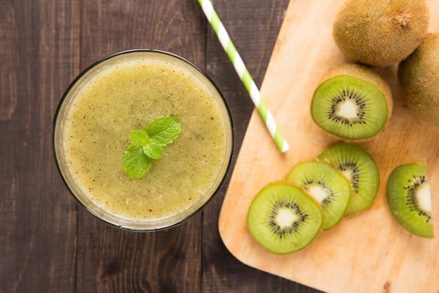 Smoothie kiwi avec des fruits frais sur une table en bois. vue de dessus