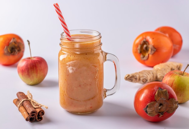 Smoothie maison de kaki, pommes, gingembre et cannelle pour augmenter l'immunité en bocal en verre sur fond blanc, format horizontal, gros plan