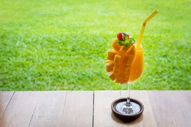 Smoothie mangue en verre sur table en bois