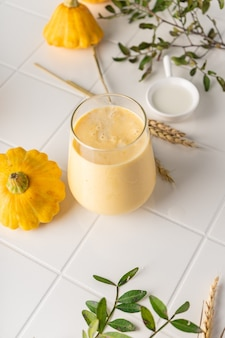 Un smoothie naturel à base de citrouille jaune. boisson d'automne avec du miel et du lait. sur fond clair, position verticale