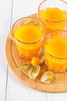 Un smoothie orange fait de physalis sur une table en bois blanche.