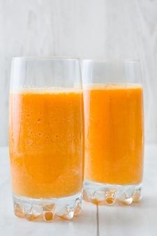 Smoothie orange, pomme et carottes sur table en bois blanc