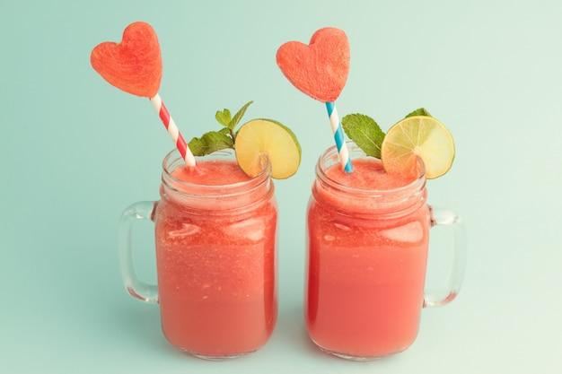 Smoothie à la pastèque fraîche dans des bocaux en verre avec des tranches de pastèque en forme de coeur sur des pailles