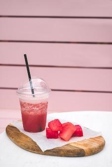 Smoothie à la pastèque fraîche. gâterie végétarienne pour toute la famille. verre fermé avec paille noire