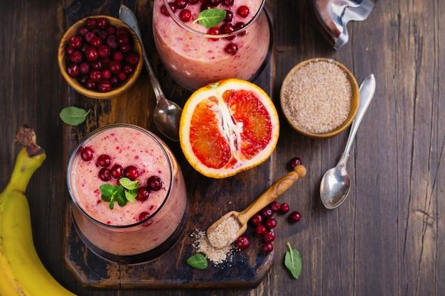 Smoothie rose rafraîchissant sain avec pomme, oranges rouges, airelle rouge et son
