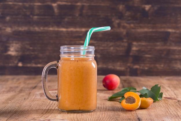 Smoothie sain d'abricot et de pêche dans une tasse en verre