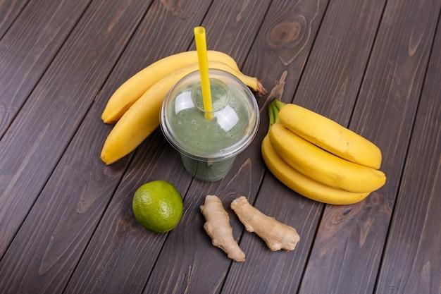 Un smoothie sain avec des bananes, de la citron et du gingembre reposent sur la table