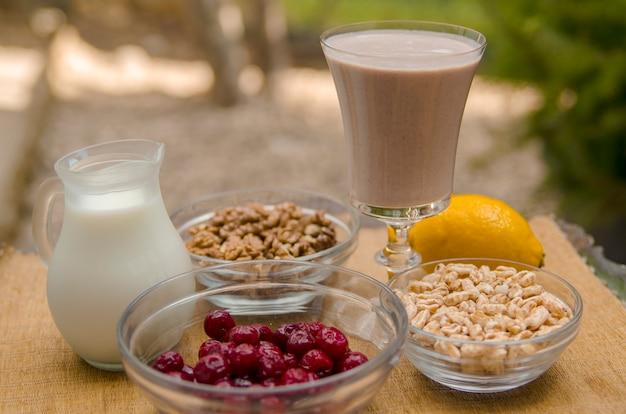 Smoothie sain avec de la cerise, de la noix, du riz expansé, du citron, du yaourt faible en gras ou du lait de soja
