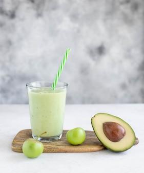 Smoothie santé à la pomme avocat-concombre dans un verre avec une paille