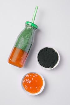 Smoothie à la spiruline dans une bouteille sur fond blanc à côté de la confiture d'agrumes et des algues séchées