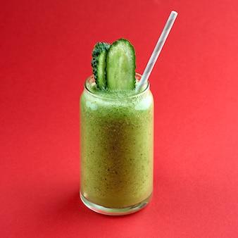 Smoothie vert au concombre sur une surface rouge