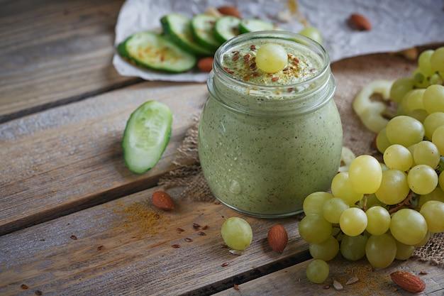 Smoothie vert bio frais avec concombre, persil, raisins et céleri sur fond de bois rustique