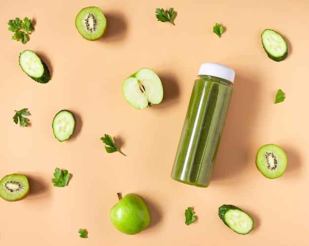 Smoothie vert dans une bouteille transparente sur fond beige. les fruits et légumes coupés sont disposés. alimentation saine, mise à plat.