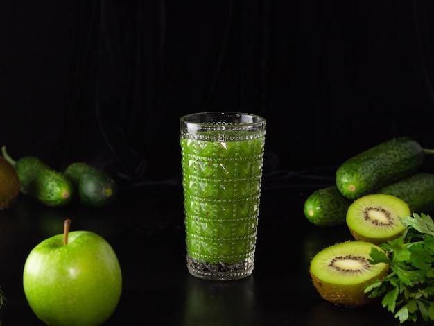 Smoothie vert dans un verre en verre sur fond noir. kiwi, pommes, concombres et légumes verts. cuisiner des aliments sains.