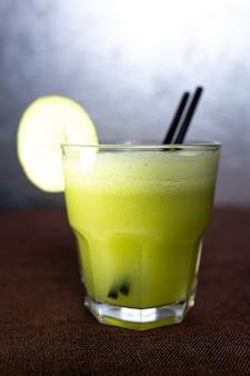 Smoothie vert dans un verre en verre avec une pomme et un tube.