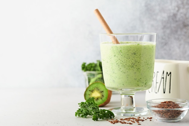 Smoothie vert détox au chou frisé, épinards et kiwi sur une ardoise gris clair