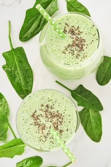 Smoothie vert détox aux épinards, graines de chia et kiwi sur ardoise gris clair, pierre ou béton