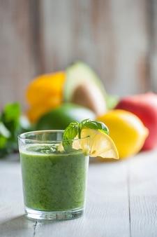 Smoothie vert de différents légumes et fruits sur table en bois