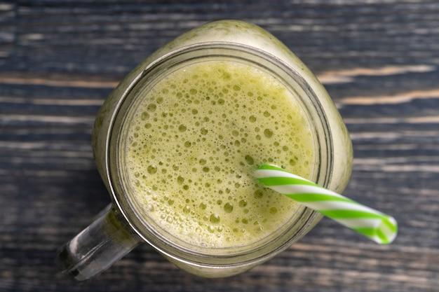 Smoothie vert frais d'avocat, kiwi, banane, miel, aneth et persil dans une tasse en verre sur fond de bois, gros plan, vue de dessus. concept d'une alimentation saine