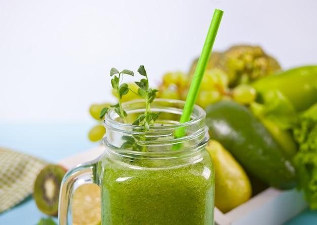 Smoothie vert frais mélangé dans un bocal en verre avec des fruits et légumes. concept de santé et de désintoxication.