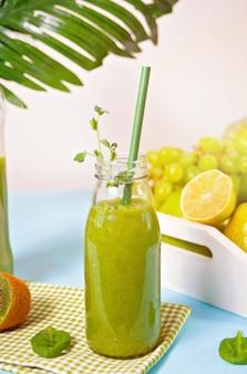 Smoothie vert frais mélangé dans une petite bouteille en verre avec des fruits et légumes. concept de santé et de désintoxication.