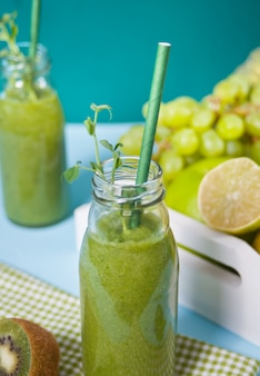 Smoothie vert frais mélangé dans de petites bouteilles en verre avec des fruits et légumes. concept de santé et de désintoxication.