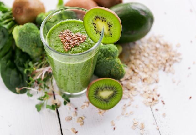 Smoothie vert frais et savoureux avec des ingrédients sur une surface en bois