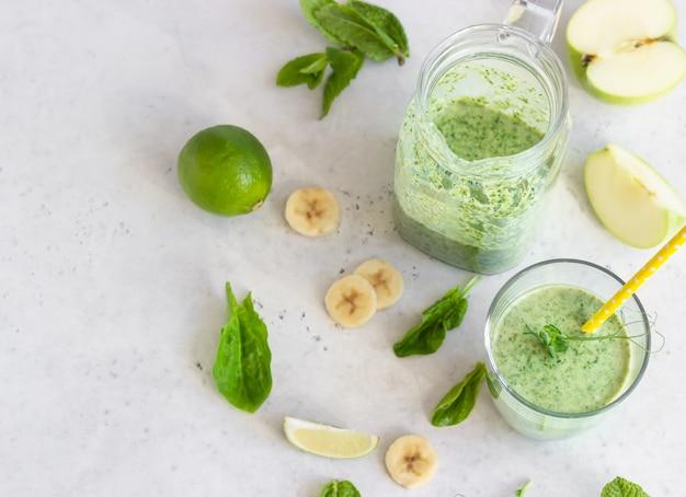 Smoothie vert mélangé avec des ingrédients dans un verre et une cruche sur une table gris clair
