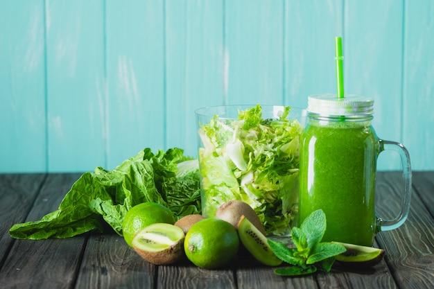 Smoothie vert mélangé avec des ingrédients sur la mise au point sélective de la table en bois.