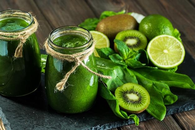 Smoothie vert mélangé avec des ingrédients sur la planche en pierre, bois
