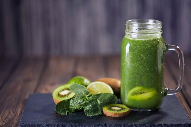 Smoothie vert mélangé avec des ingrédients sur la planche de pierre, mise au point sélective de table en bois