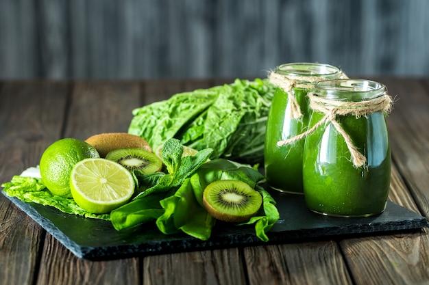 Smoothie vert mélangé avec des ingrédients sur le plateau en pierre, table en bois