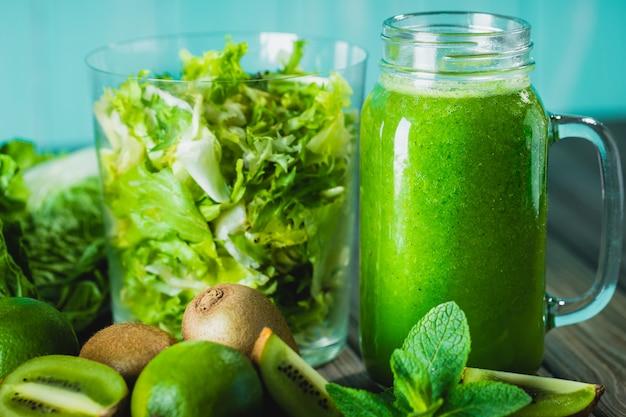 Smoothie vert mélangé avec des ingrédients sur une table en bois