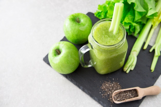 Smoothie vert mélangé avec des ingrédients.