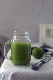 Smoothie vert organique frais aux épinards, concombre sur une vaisselle blanche